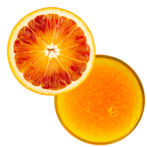 A sliced tarocco orange with a juice glass